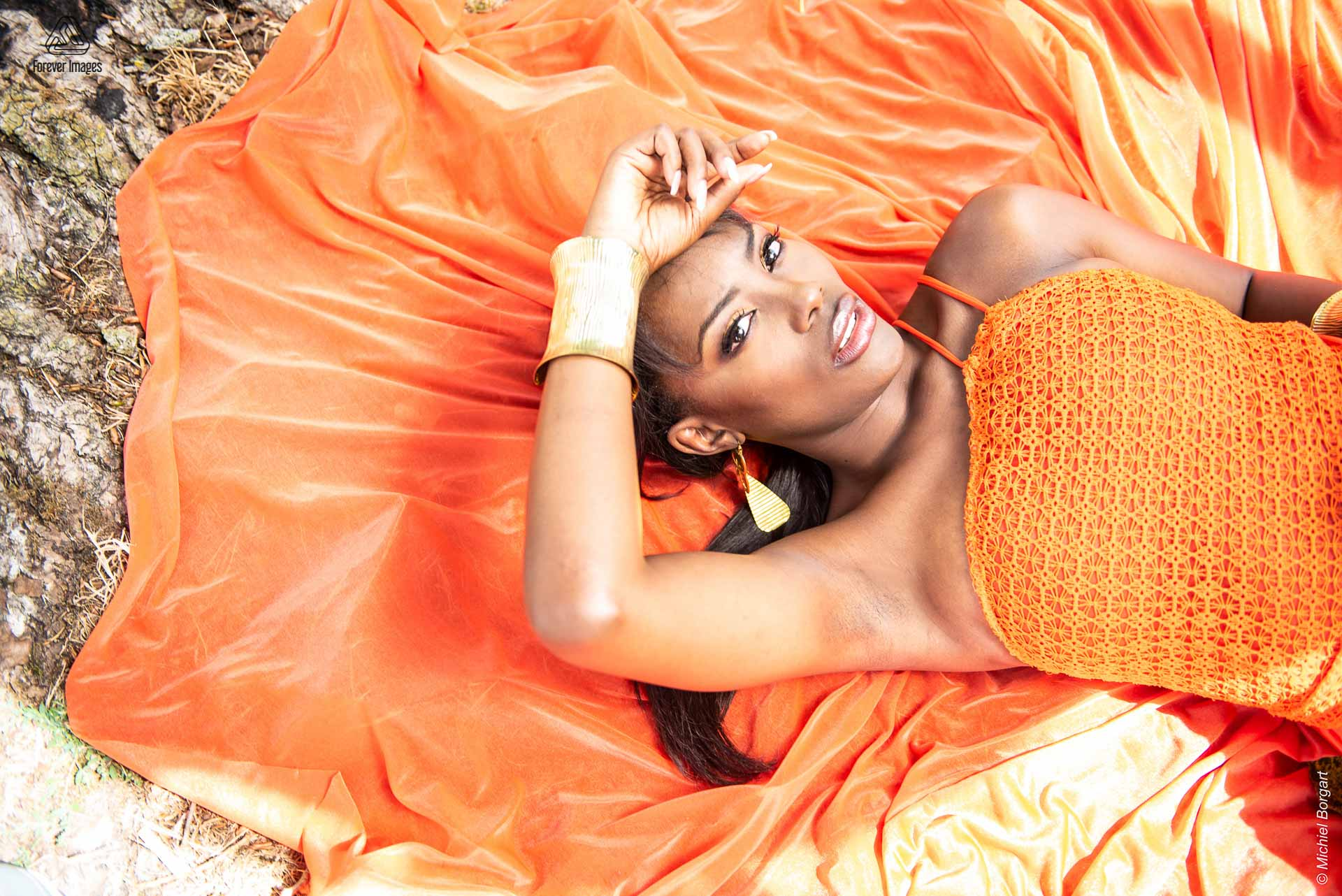 Fashion photo urben shoot orange dress on the floor side | Mariana Pietersz David Cardenas Miss Avantgarde | Fashion Photographer Michiel Borgart - Forever Images.
