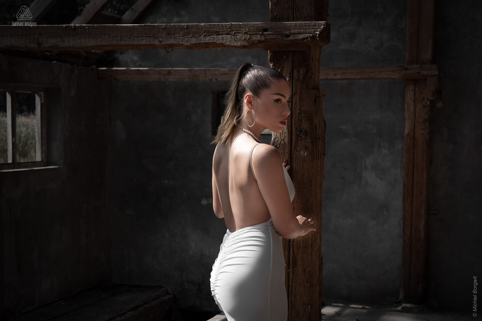 Portrait photo urbex white dress beautiful lady in old barn near wooden pillar | Floriana Horta | Portrait Photographer Michiel Borgart - Forever Images.