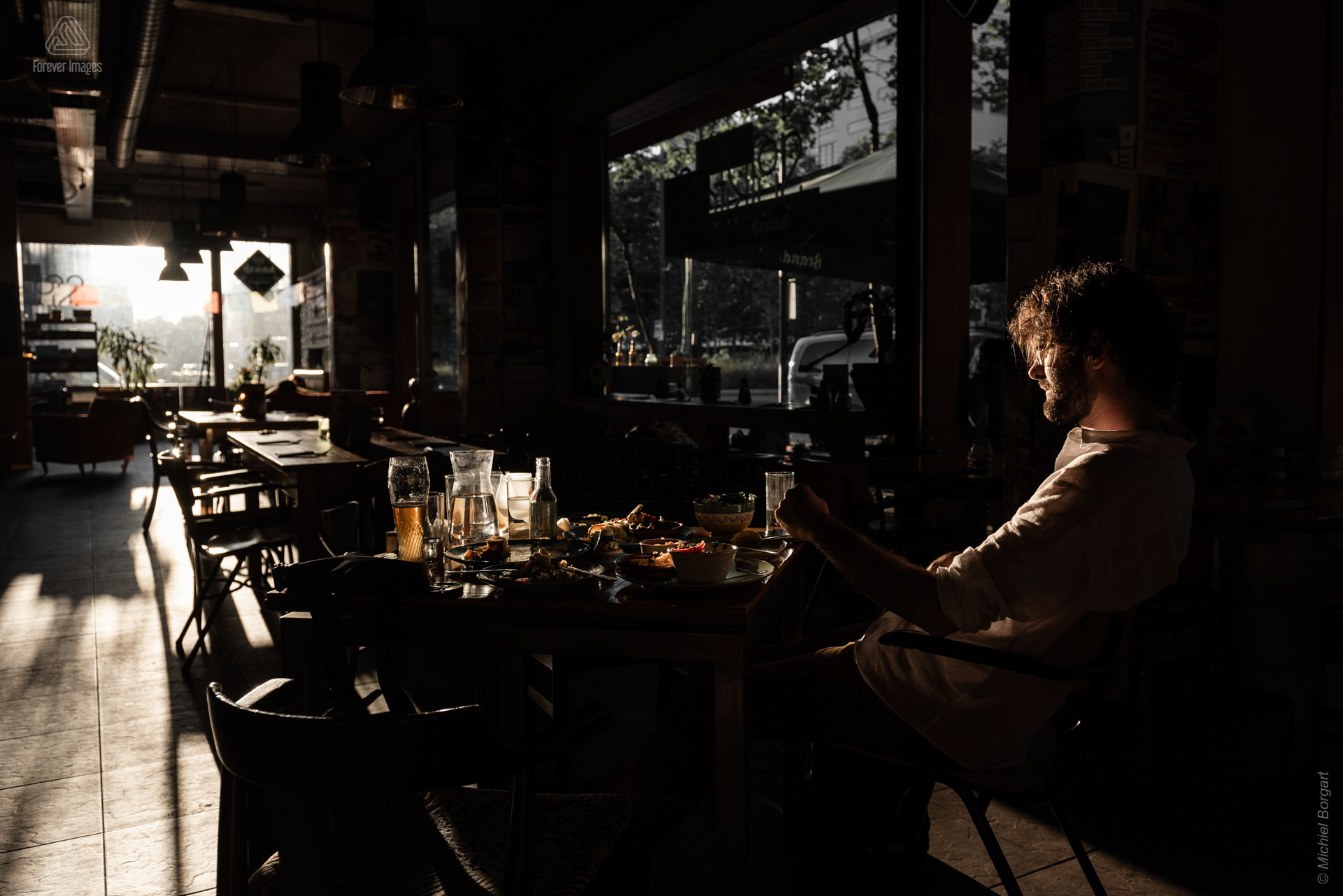 Portrait photo low key man sitting at table in bar | Strijp | Portrait Photographer Michiel Borgart Forever Images.