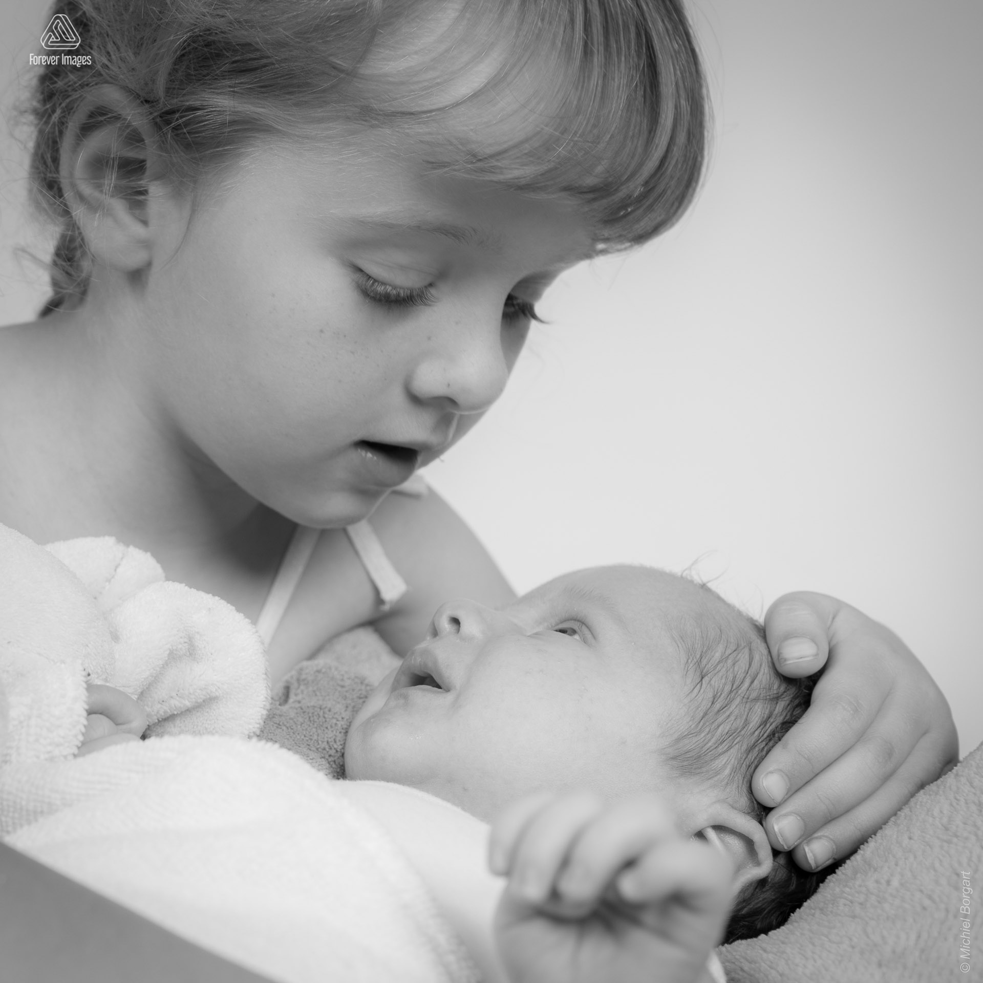 Portrait photo newborn baby new born being held by his big sister | Rozelinde Kylian | Portrait Photographer Michiel Borgart Forever Images.
