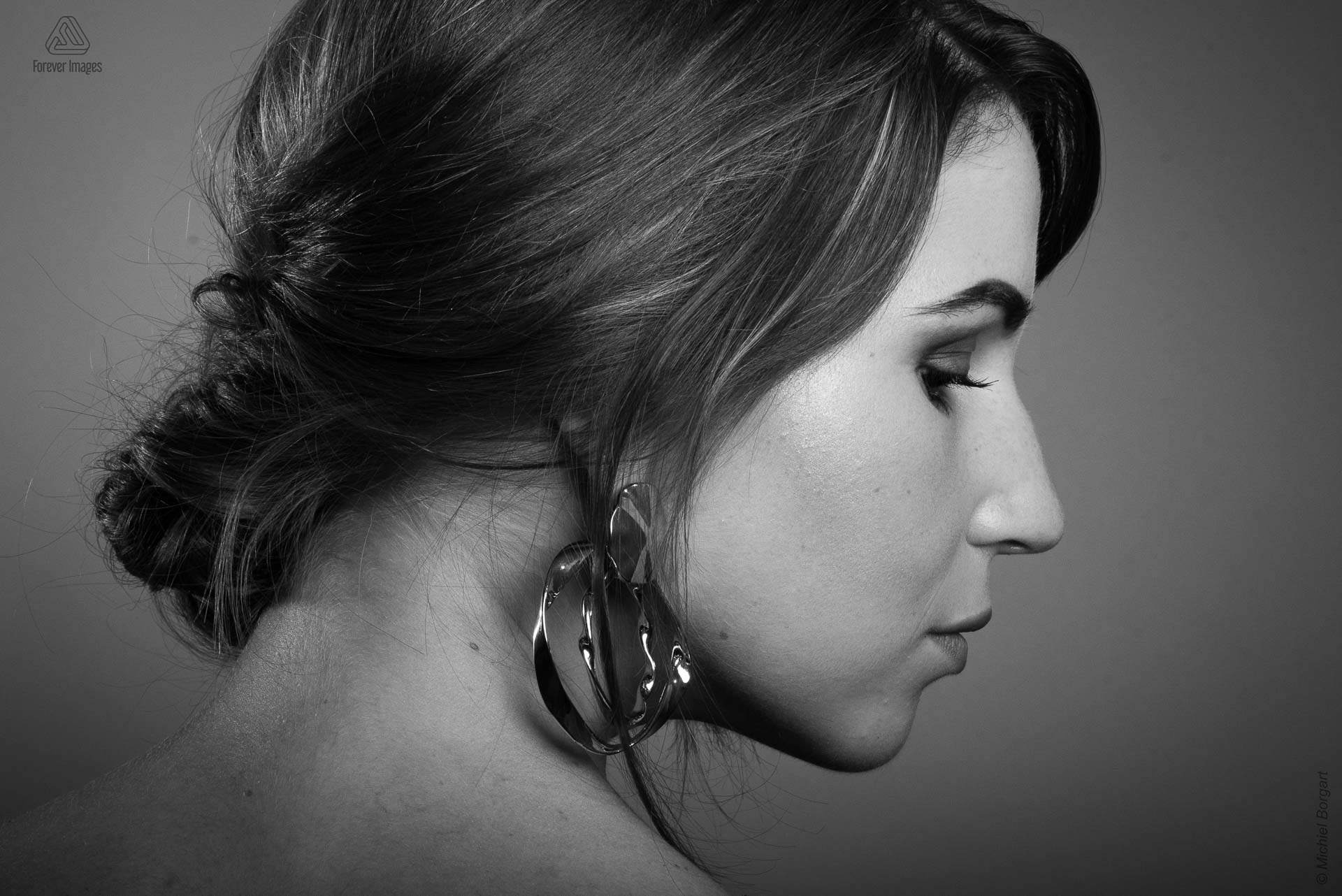 Portrait photo black and white young lady big earrings looking to the side | Noah Doornebal | Portrait Photographer Michiel Borgart - Forever Images.