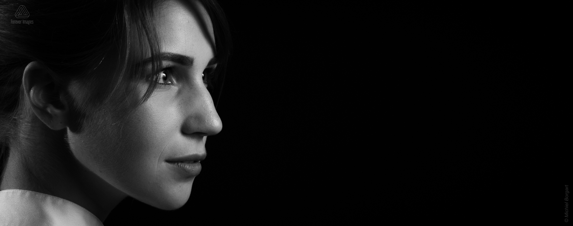Portrait photo black and white young lady close-up looking aside low key | Noah Doornebal | Portrait Photographer Michiel Borgart - Forever Images.